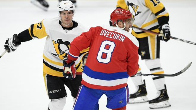 Washington Capitals left wing Alex Ovechkin (8), of Russia, skates next to Pittsburgh Penguins center Sidney Crosby (87) during the third period of an NHL hockey game, Sunday, Feb. 2, 2020, in Washington. The Penguins won 4-3.