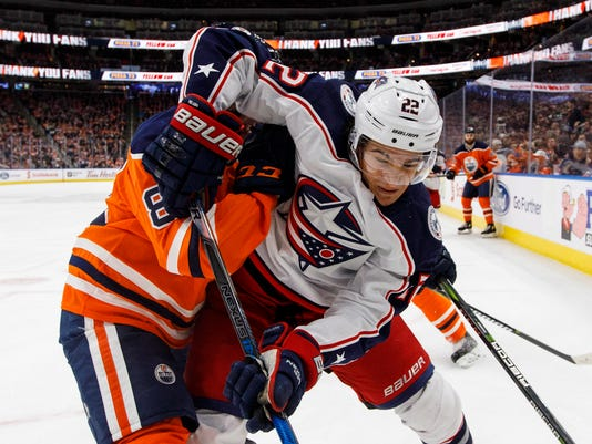 Columbus Blue Jackets' Sonny Milano (22) and Edmonton Oilers' Matthew Benning (83) battle for the puck during first period NHL hockey action in Edmonton, Alberta, on Tuesday March 27, 2018. (Jason Franson/The Canadian Press via AP)