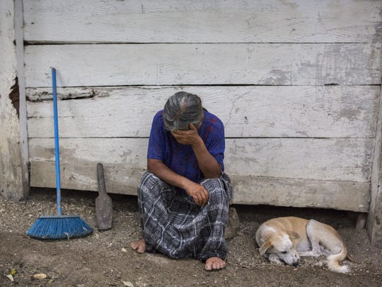 Elvira Choc, 59, Jakelin Amei Rosmery Caal's grandmother, rests her head on her hand in front of her house in Raxruha, Guatemala, on Saturday, Dec. 15, 2018.