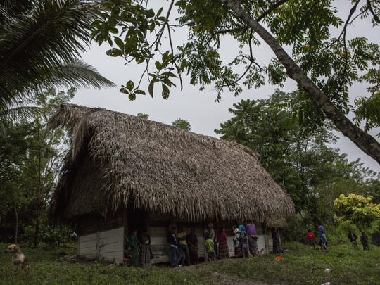 Neighbors gather around Claudia Maquin's house in Raxruha, Guatemala, on Saturday, Dec. 15, 2018. Her daughter, 7-year-old Jakelin Amei Rosmery Caal, used to sleep here with her parents and three siblings. The small wooden house has a straw roof, dirt floors, a few bedsheets and a fire pit for cooking.