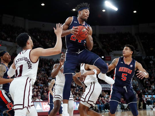 Auburn forward Anfernee McLemore (24) hauls down a rebound in front of Mississippi State guard Quinndary Weatherspoon (11) during the first half of an NCAA college basketball game in Starkville, Miss., Saturday, Jan. 26, 2019. (AP Photo/Rogelio V. Solis)