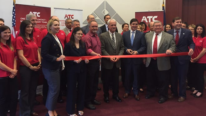 Lafayette business officials and employees of ATC Group Services celebrate the relocation of the company's headquarters back to Lafayette.