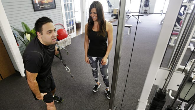 Ricardo Arguello works out under the watchful eye of trainer Maria Munoz at Evolve Personal Training in Appleton.