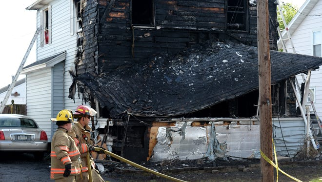 Syracuse firefighters begin to clean up at the scene of a fatal fire Friday  in Syracuse.