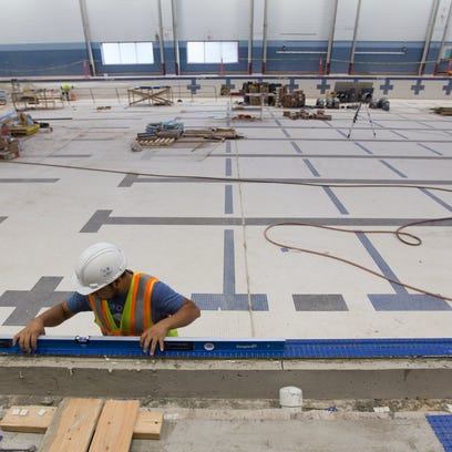 Workers lay down and clean tile around the main pool
