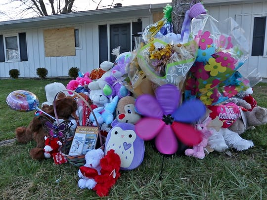 A memorial for 1-year-old Malaysia Robson sits in front