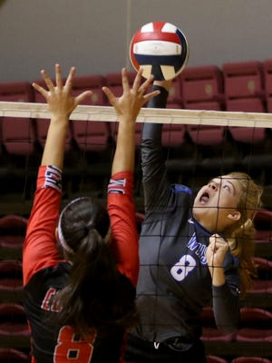 Windthorst's Kora Pennartz spikes the ball but is blocked by Wichita Falls High School's Amaya Saenz Tuesday, Aug. 8, 2017, during Battlie in the Dome in D.L. Ligon Coliseum.