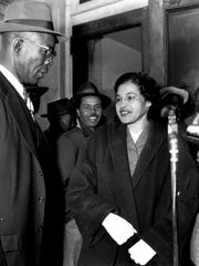Rosa Parks holds up her arrest number as her mug is taken, left, and Rosa Parks and E.D. Nixon,  former president of the Alabama NAACP, talk at her March 19, 1956, trial at the Montgomery courthouse.