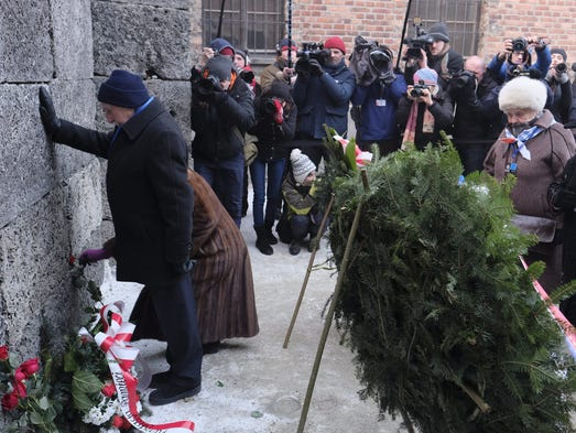 Former prisoners place candles and flowers at the Death