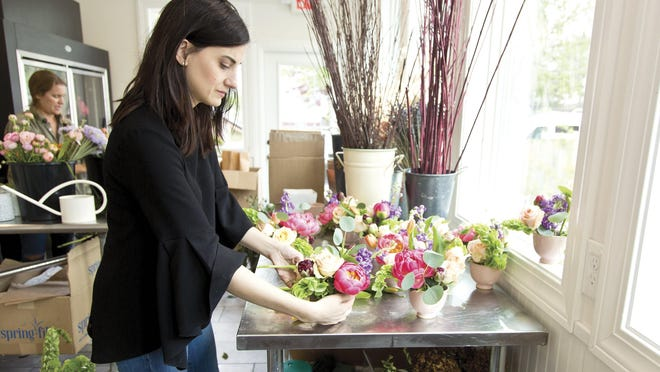 Co-owner Sarah Lagroterria works on a floral arrangement at Flowers & Bread Society on North High Street in Clintonville.