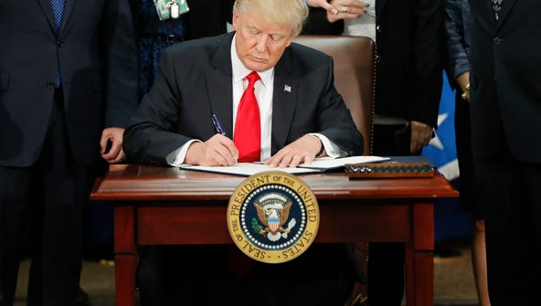 President Donald Trump signs an executive order for