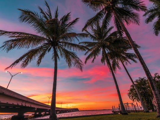 Midpoint Memorial Bridge, palms and sunset on the Caloosahatchee.