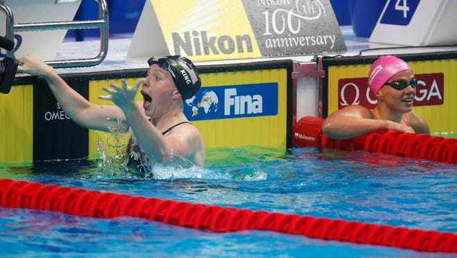 Lilly King, left, celebrates after setting a world record in the women's 100-meter breaststroke and beating Russian rival Yuliya Efimova.