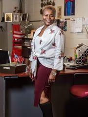 Angela Ringgold wears a cotton floral shirt with waist bow from SteinMart; white knit tank top by Michael Kors; burgundy knit pencil skirt from Saks Fifth Off the Avenue; and black stretch boots by Ralph Lauren.