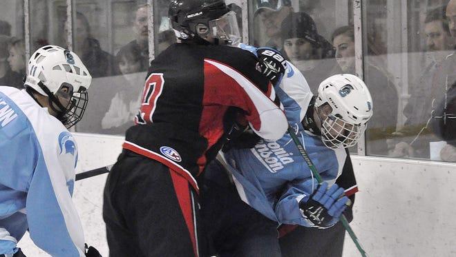 Livonia Churchill's Joe Wozniak attempts to check Livonia Stevenson's Nate Sudek during Wednesday's game.