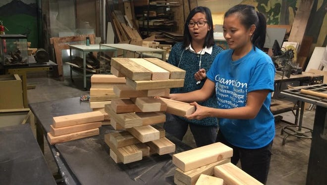 Earlham students test the giant Jenga game that will be part of Saturday afternoon's free activities at the campus' Joseph Moore Museum.