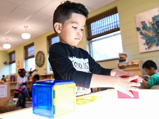 A preschool student builds on a light-table Monday,