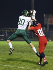 Kennedy's Christian Reyes tries to block a pass to Regis's Sam Nieslanik in a Tri-River Conference game Thursday, Oct. 8, 2015, in Mount Angel.