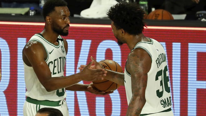 Boston Celtics guard Kemba Walker (8) and Boston Celtics guard Marcus Smart (36) celebrate after defeating the Philadelphia 76ers in Game 3 of their first-round playoff series, Friday, Aug. 21, 2020, in Lake Buena Vista, Fla.