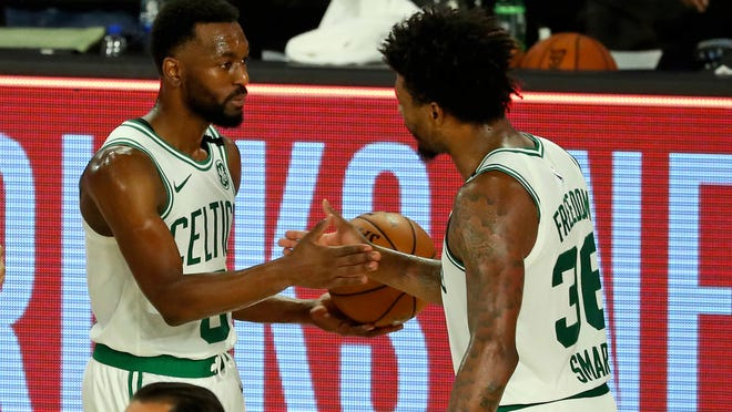 Boston Celtics guard Kemba Walker (8) and Boston Celtics guard Marcus Smart (36) celebrate after defeating the Philadelphia 76ers in Game 3 of an NBA basketball first-round playoff series, Friday, Aug. 21, 2020, in Lake Buena Vista, Fla.