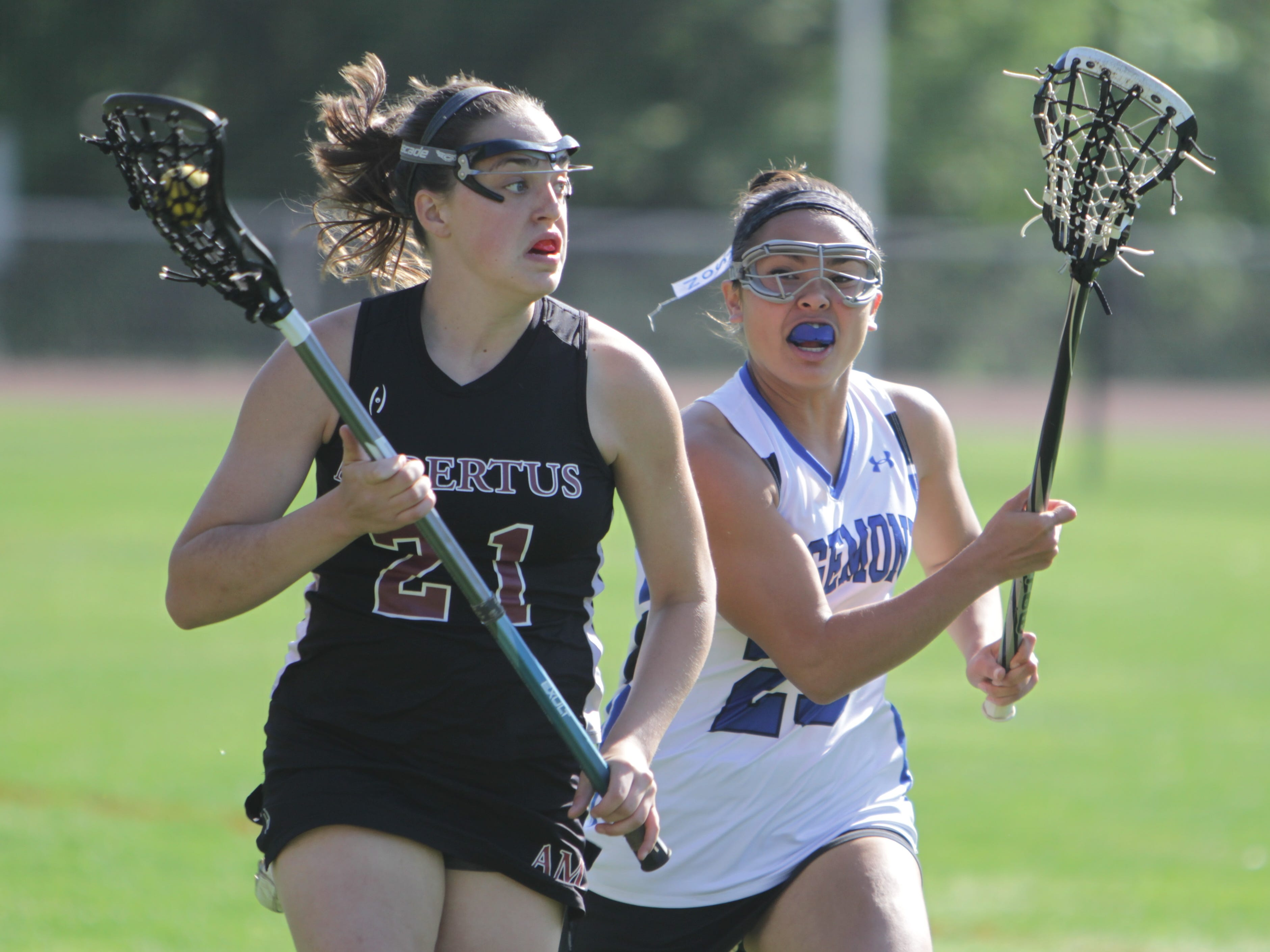 Albertus Magnus' Amanda Silvestri runs up the field and is guarded by Edgemont's Dani Myerson during a Class C sectional tournament first round game at Edgemont High School. Edgemont won 10-8.