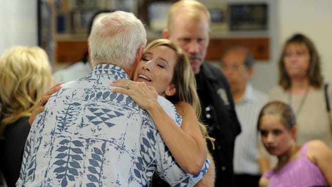 Jennifer Osler, widow of Ryan Osler, hugs some of the people who attended the unveiling of her husband's memorial at Ventura County Fire Station No. 42 in Moorpark on Thursday afternoon.