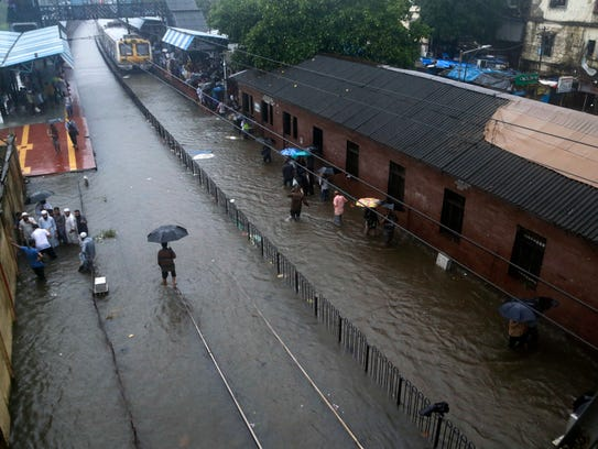 People walk through a flooded train station during
