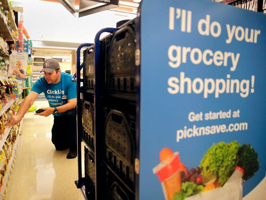 Patrick Hanley, an employee at Pick 'n Save, fills a grocery order from ClickList Friday, Aug. 4, 2017, in Appleton, Wis. ClickList allows customers to order their groceries online and have them ready for pickup at the store.
