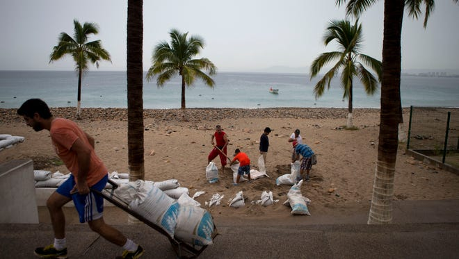 Residents prepare for the arrival of Hurricane Patricia filling sand bags to protect beachfront businesses, in Puerto Vallarta, Mexico, Friday, where Palm Springs Unified School District spokeswoman Joan Boiko is vacationing.