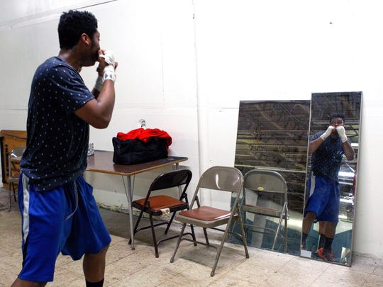 Michael Fletcher, 19, of Colerain, practices his boxing form in front of a mirror Wednesday during recreational time for Fighting Chance. The non-profit uses boxing as an outlet for kids in the community to create and achieve goals in sports and academics.