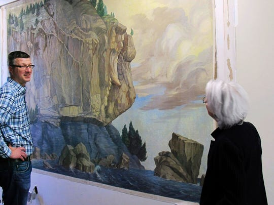Devin Colman of the Vermont Division of Historic Preservation and Janie Cohen, director of the Fleming Museum at the University of Vermont, look at a painting of a prominent Lake Champlain geological formation Tuesday.