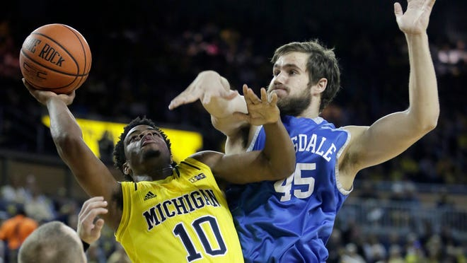 Derrick Walton Jr. #10 of the Michigan Wolverines takes a shot against Nick Archer #45 of the Hillsdale College Chargers during the first half of Saturday's game.