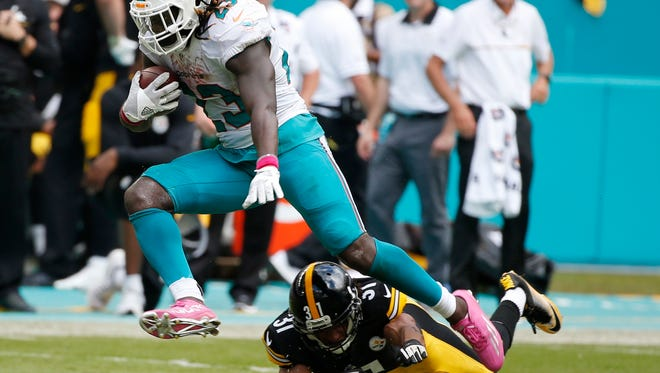 Miami Dolphins running back Jay Ajayi (23) avoids a tackle by Pittsburgh Steelers cornerback Ross Cockrell (31), during the second half of Sunday's game at Hard Rock Stadium in Miami.