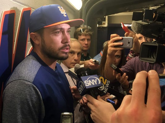 New York Mets catcher Travis d'Arnaud, left, speaks with members of the media in New York. Friday, April 13, 2018, after announcing that he will have Tommy John surgery.  D'Arnaud has a partial tear of the ulnar collateral ligament in his right elbow and will have the surgery next week. (AP Photo/Ron Blum)