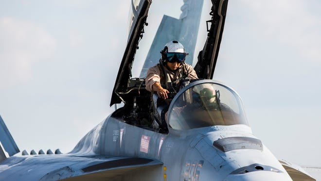 Lieutenant Pete Santos climbs out of the cockpit of the US Navy F-18 Rhino Super Hornet jet after flying it into Anderson Regional Airport for the upcoming airshow on Thursday, October 20, 2016 in Anderson.