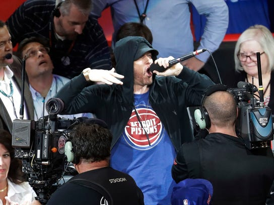 Eminem yells to the crowd before the start of an NBA