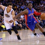 Detroit Pistons guard Reggie Jackson, right, dribbles next to Golden State Warriors star Stephen Curry on March 11, 2015, in Oakland, Calif.