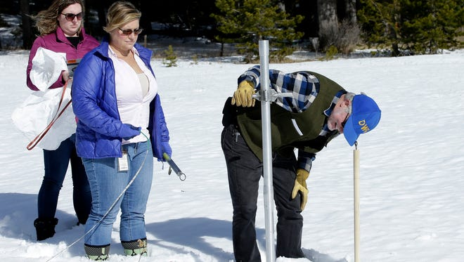 Frank Gehrke, right, chief of the California Cooperative Snow Surveys Program, for the Department of Water Resources, checks the snowpack depth as Courtney Obergfell, left, and Michelle Mead, center, both of the National Weather Service, look on during the second snow survey of the season Thursday, Feb. 1, 2018, near Echo Summit, Calif.