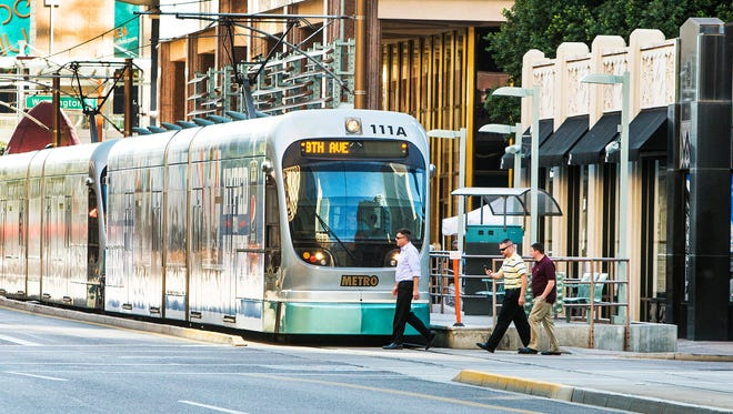 A light rail train makes its stop heading north on Central Avenue just north of Washington in downtown Phoenix.
