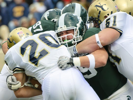 Blake Pacheco (center) MSU gets off a block by David