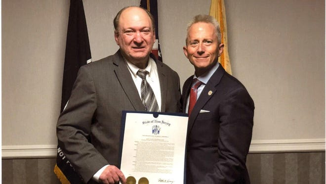 """Stephen I. Plevins accepts a Joint Legislative Resolution """"in grateful recognition of his extraordinary record of service and dedication to his fellow citizens"""" from State Sen. Jeff Van Drew."""