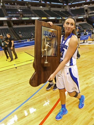 Heritage Christian's #23 Peyton Fallis carries the team trophy plaque after they won the IHSAA Girls Class 2A girls basketball state finals game at Bankers Life Fieldhouse, Saturday, March 7, 2015.  Heritage Christian won the game against Ft. Wayne Canterbury 73-53.