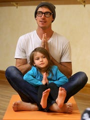 Jason Henkel and his daughter Via Castaneda-Henkel, 4, participate in a toddler yoga class at Body & Soul Wellness Center and Spa in Dubuque.