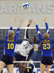 Pittsford Sutherland's Santita Ebangwese, center, hits over the block of Irondequoit's Kylee Kanealy (10) and Ally Vanacker during the Class A Section 5 Championship.