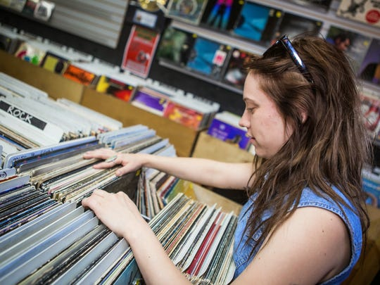 A customer browses titles at Revolver Records in Phoenix for Record Store Day on Saturday, April 18, 2015.