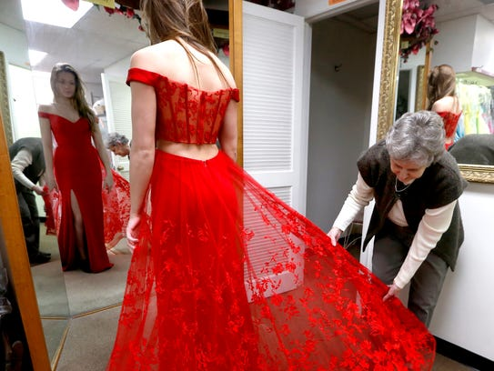 Abby Meeks gets a glimpse of her dress while Helen Wilson pulls out the train of the skirt. Wilson has owned Bridal Country in Smyrna for more than 40 years and lace is popular for promgoers this year.