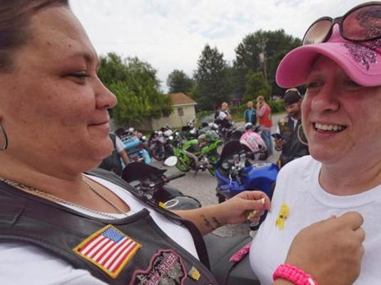 """Kimberly """"Kharma"""" Stahle, left, pins a yellow ribbon on Melissa Palumbo to symbolize stop the violence before the group starts the ride in Springettsbury township."""
