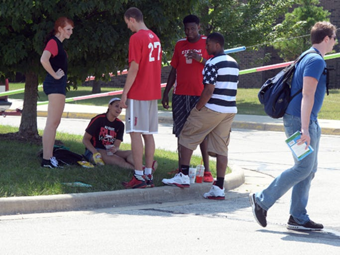 Students share a bit of shade during an event for the start of classes beginning at Indiana University East called Back with the Pack 2014 Tuesday, Aug. 26, 2014.