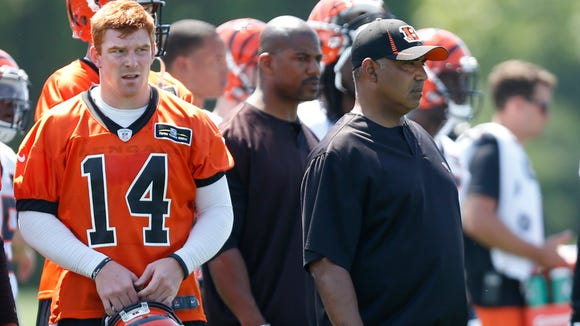 Quarterback Andy Dalton (14) and head coach Marvin Lewis watch drills during open practice  in May of 2013.