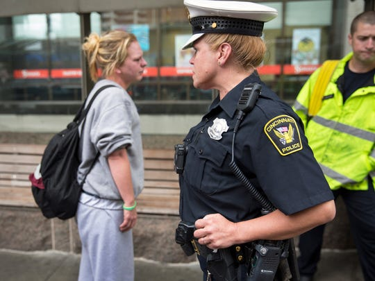 "Cincinnati Police Officer Christine Barry, firefighter/ paramedic Brandon Jackson talk to a woman on Fountain Square after being called out on a ""near overdose"" situation."